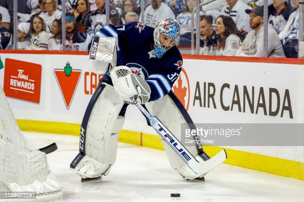Goaltender Connor Hellebuyck of the Winnipeg Jets plays the puck behind the net during second period action against the St Louis Blues in Game Five...