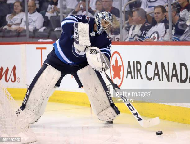 Goaltender Connor Hellebuyck of the Winnipeg Jets plays the puck behind the net during second period action against the Nashville Predators in Game...