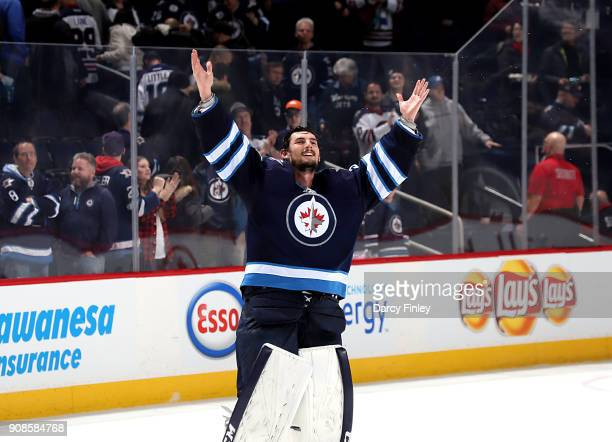Goaltender Connor Hellebuyck of the Winnipeg Jets pumps up the fans after receiving first star honors following a 10 shutout victory over the...