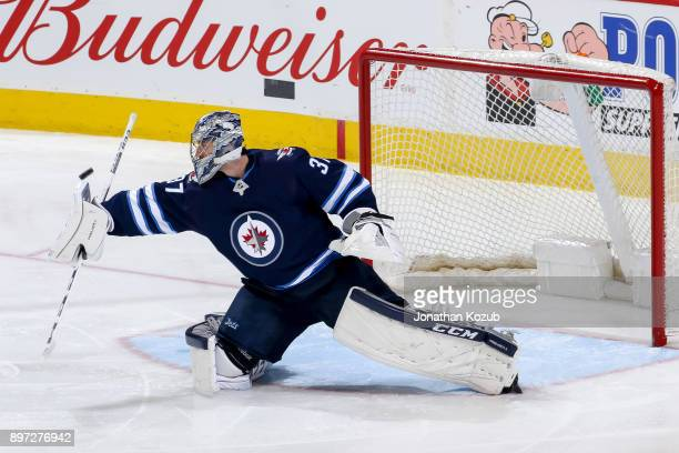 Goaltender Connor Hellebuyck of the Winnipeg Jets redirects the puck wide of the net during third period action against the St Louis Blues at the...