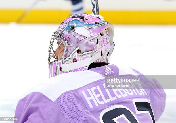 Goaltender Connor Hellebuyck of the Winnipeg Jets sports a lavender jersey and mask during the pregame warm up in support of Hockey Fights Cancer...