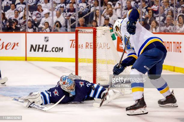 Goaltender Connor Hellebuyck of the Winnipeg Jets sprawls on the ice as he battles for the puck against Robert Thomas of the St Louis Blues during...