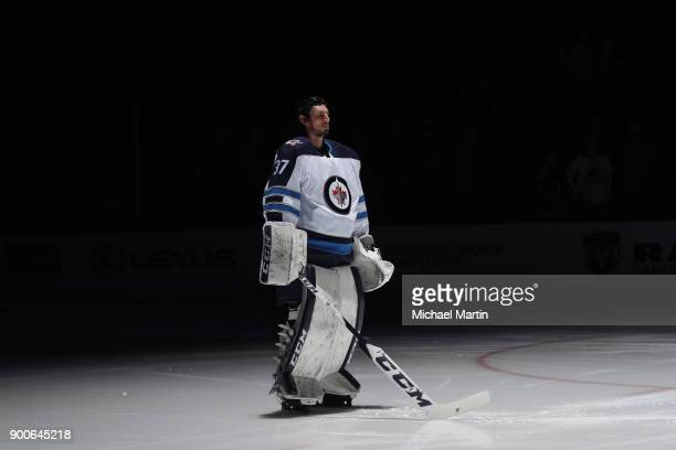 Goaltender Connor Hellebuyck of the Winnipeg Jets stands during introductions prior to the game against the Colorado Avalanche at the Pepsi Center on...
