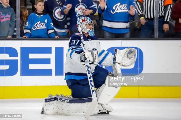 Goaltender Connor Hellebuyck of the Winnipeg Jets stretches during the pregame warm up prior to NHL action against the Vegas Golden Knights at...