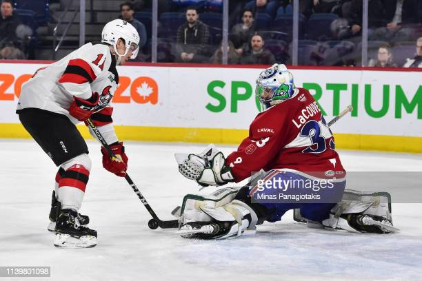 Goaltender Connor LaCouvee of the Laval Rocket makes a pad save on Brett Seney of the Binghamton Devils during the AHL game at Place Bell on March 27...