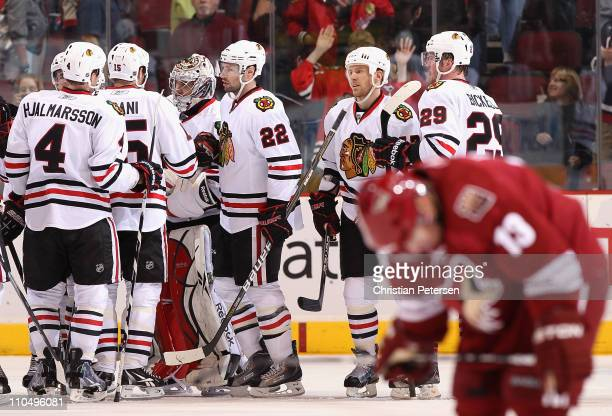 Goaltender Corey Crawford of the Chicago Blackhawks celebrates with teammates after defeating the Phoenix Coyotes in the NHL game at Jobingcom Arena...