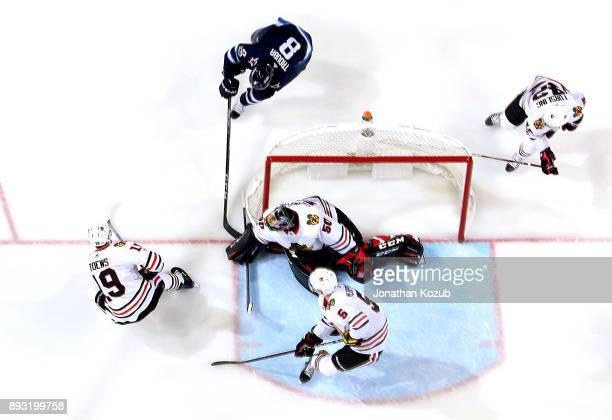 Goaltender Corey Crawford of the Chicago Blackhawks covers up the puck with his glove as Jacob Trouba of the Winnipeg Jets tries to poke it loose...