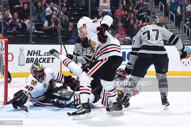 Goaltender Corey Crawford of the Chicago Blackhawks dives for the puck while Carl Dahlstrom falls to the ice as Kyle Clifford and Jeff Carter of the...