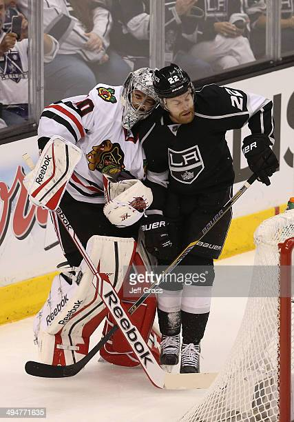 Goaltender Corey Crawford of the Chicago Blackhawks is checked by Trevor Lewis of the Los Angeles Kings in the first period in Game Six of the...