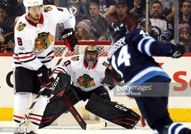 Goaltender Corey Crawford of the Chicago Blackhawks keeps his eye on the puck as Josh Morrissey of the Winnipeg Jets shoots it down the ice during...