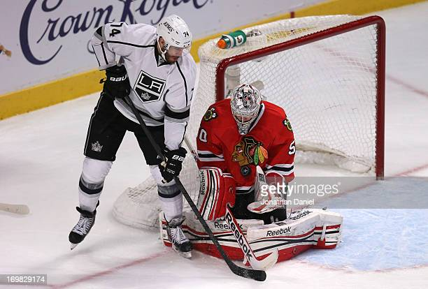 Goaltender Corey Crawford of the Chicago Blackhawks makes a save as Dwight King of the Los Angeles Kings tries for the deflection in the first period...