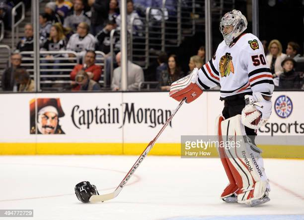 Goaltender Corey Crawford of the Chicago Blackhawks moves the helmet of Jeff Carter of the Los Angeles Kings away in the second period in Game Six of...