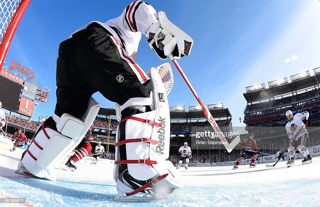Goaltender Corey Crawford #50 of the Chicago Blackhawks passes the puck from his crease area to defenseman Brent Seabrook #7 during the 2015 Bridgestone NHL Winter Classic against the Washington Capitals at Nationals Park on January 1, 2015 in Washington, D.C. The Capitals defeated the Blackhawks 3-2.
