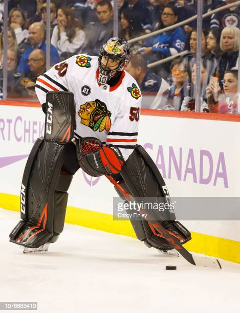 Goaltender Corey Crawford of the Chicago Blackhawks plays the puck along the boards during first period action against the Winnipeg Jets at the Bell...