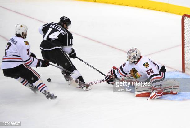 Goaltender Corey Crawford of the Chicago Blackhawks poke checks the puck off the stick of Justin Williams of the Los Angeles Kings in the second...