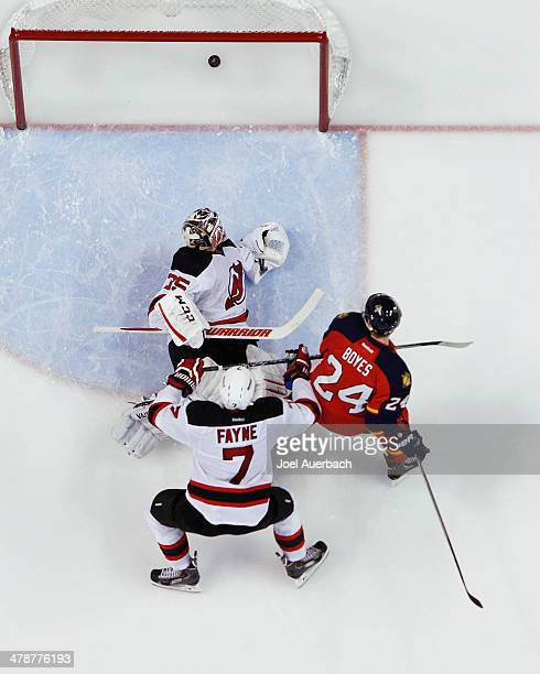 Goaltender Cory Schneider of the New Jersey Devils looks back into the net as Brad Boyes of the Florida Panthers scores a third period goal at the...