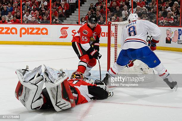 Goaltender Craig Anderson dives to stop Brandon Prust of the Montreal Canadiens as teammate Erik Karlsson of the Ottawa Senators tries to defend in...