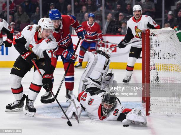 Goaltender Craig Anderson of the Ottawa Senators dives for the puck while teammate Thomas Chabot defends against the Montreal Canadiens during the...
