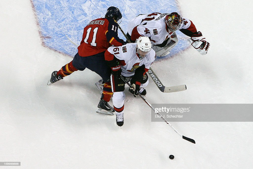 Goaltender Craig Anderson #41of the Ottawa Senators defends the net with the help of teammate Andre Benoit #61against Jonathan Huberdeau #11of the Florida Panthers at the BB&T Center on January 24, 2013 in Sunrise, Florida.