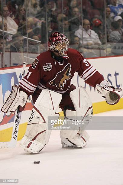 Goaltender Curtis Joseph of the Phoenix Coyotes controls the puck behind the net against the Columbus Blue Jackets during their NHL game on March 3...