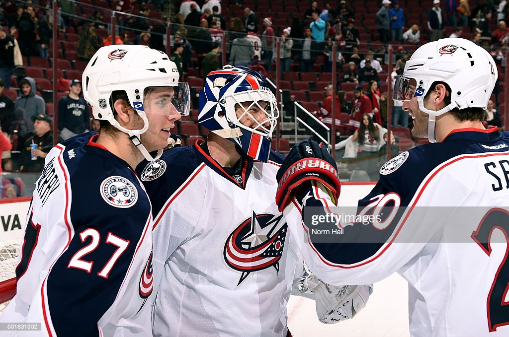 Goaltender Curtis McElhinney #30 of the Columbus Blue Jackets is congratulated by teammates Ryan Murray #27 and Brandon Saad #20 after a 7-5 victory against the Arizona Coyotes at Gila River Arena on December 17, 2015 in Glendale, Arizona.