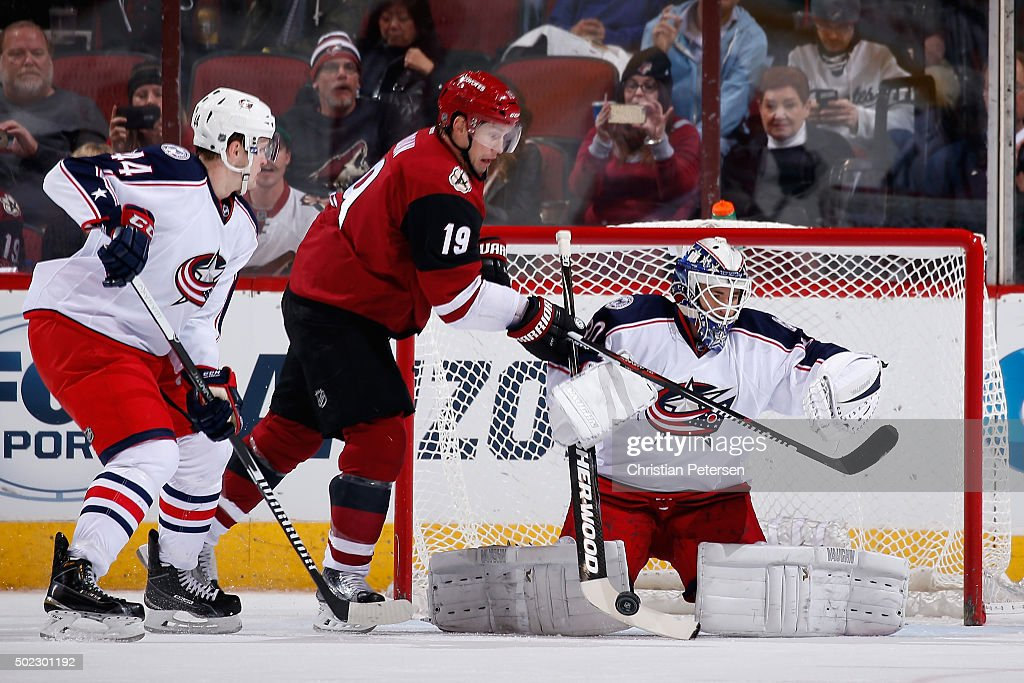 Goaltender Curtis McElhinney #30 of the Columbus Blue Jackets makes a save as Shane Doan #19 of the Arizona Coyotes skates in during the NHL game at Gila River Arena on December 17, 2015 in Glendale, Arizona. The Blue Jackets defeated the Coyotes 7-5.