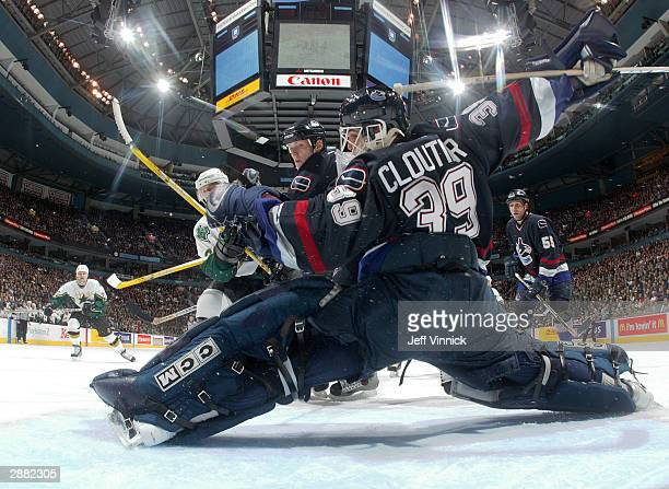 Goaltender Dan Cloutier of the Vancouver Canucks stretches across the crease as teammate Bryan Allen tries to stop the shot of David Oliver of the...