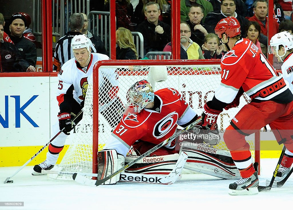 Goaltender Dan Ellis #31 of the Carolina Hurricanes defends the goal against Chris Neil #25 of the Ottowa Senators during play at PNC Arena on February 1, 2013 in Raleigh, North Carolina. The Hurricanes won 1-0.