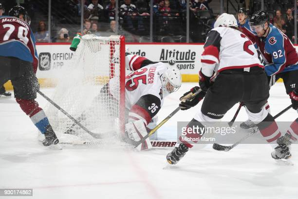 Goaltender Darcy Kuemper of the Arizona Coyotes covers the puck next to teammate Luke Schenn and Nathan MacKinnon and Gabriel Landeskog of the...