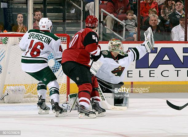 Goaltender Darcy Kuemper of the Minnesota Wild makes a glove save as Antoine Vermette of the Arizona Coyotes and Jared Spurgeon of the Wild skate in...
