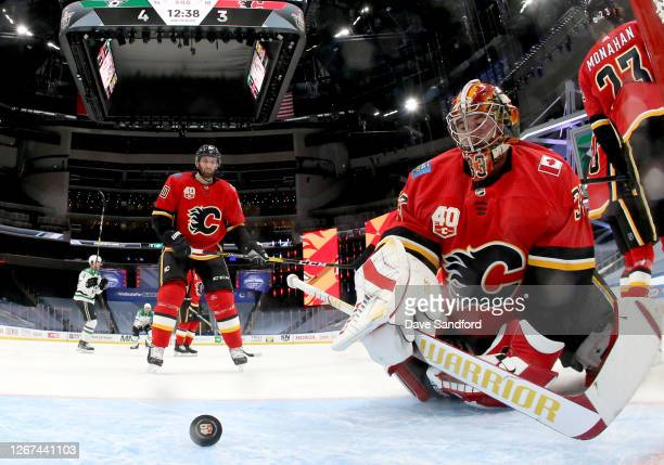 Goaltender David Rittich and Derek Forbort of the Calgary Flames look at the puck after it went in the net on a shot by Joe Pavelski of the Dallas...