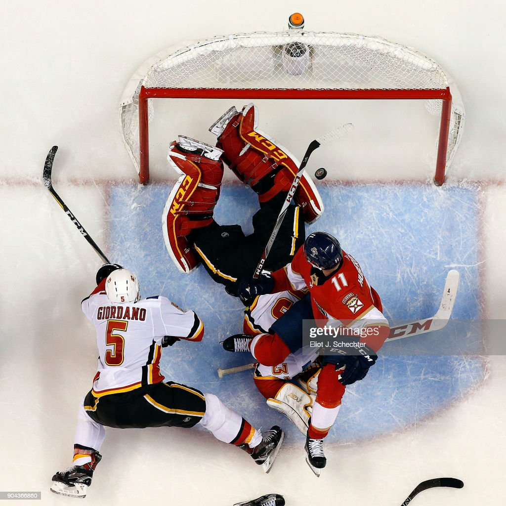 Goaltender David Rittich #33 of the Calgary Flames defends the net with the help of teammate Mark Giordano #5 against Jonathan Huberdeau #11 of the Florida Panthers at the BB&T Center on January 12, 2018 in Sunrise, Florida.