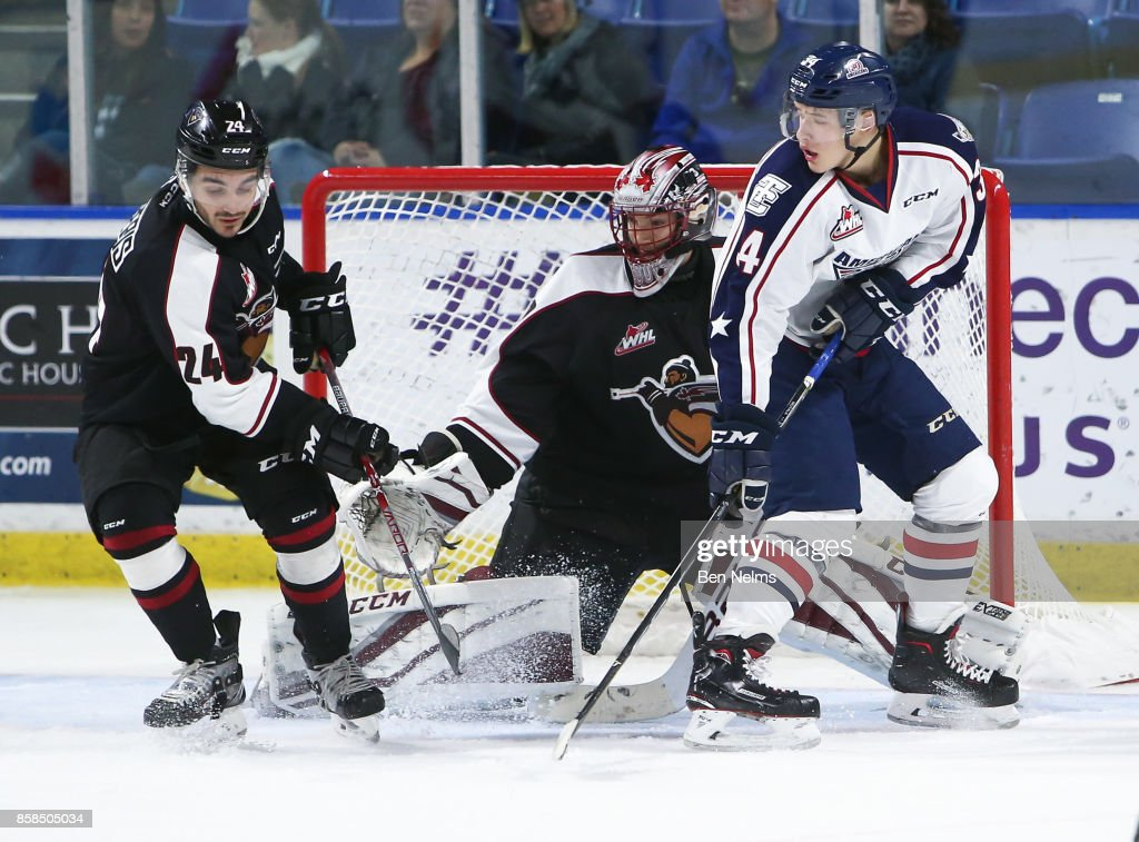 Goaltender David Tendeck #30 of the Vancouver Giants makes a save near teammate Matt Barberis #24 and Sasha Mutala #34 of the Tri-City Americans during the third period of their WHL game at the Langley Events Centre on October 6, 2017 in Langley, British Columbia, Canada.