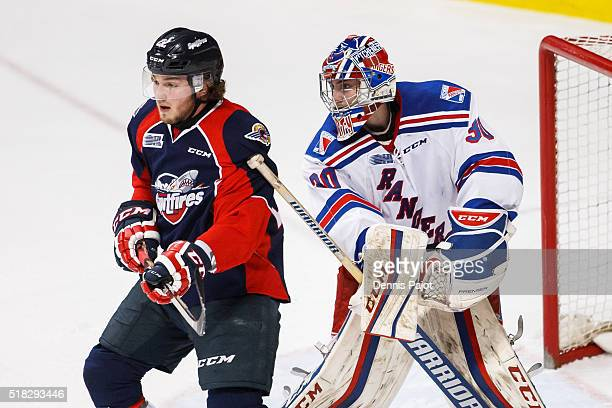 Goaltender Dawson Carty of the Kitchener Rangers battles against forward Brendan Lemieux of the Windsor Spitfires during game 4 of the Western...