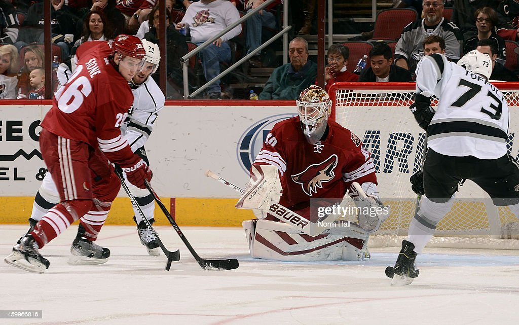 Goaltender Devan Dubnyk #40 of the Arizona Coyotes deflects the puck away from Michael Stone #26 of the Coyotes and Dwight King #74 of the Los Angeles Kings during the third period at Gila River Arena on December 4, 2014 in Glendale, Arizona.
