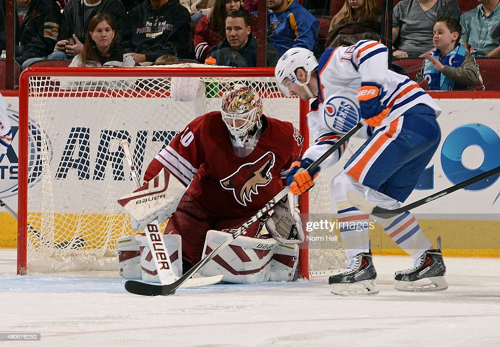 Goaltender Devan Dubnyk #40 of the Arizona Coyotes looks to make a save on the shot attempt by Teddy Purcell #16 of the Edmonton Oilers during the third period at Gila River Arena on December 16, 2014 in Glendale, Arizona.
