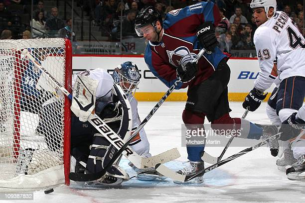 Goaltender Devan Dubnyk of the Edmonton Oilers makes a save against Philippe Dupuis of the Colorado Avalanche at the Pepsi Center on February 23 2011...