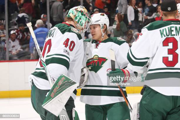 Goaltender Devan Dubnyk of the Minnesota Wild celebrates a win against the Colorado Avalanche with teammate Mikael Granlund at the Pepsi Center on...