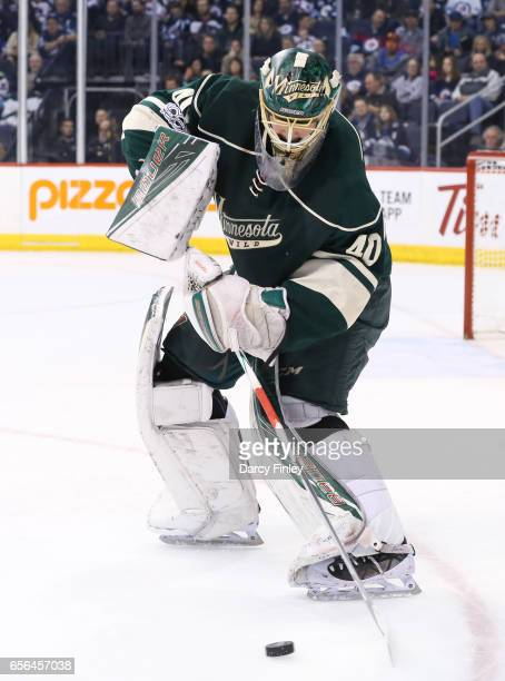 Goaltender Devan Dubnyk of the Minnesota Wild plays the puck during first period action against the Winnipeg Jets at the MTS Centre on March 19 2017...