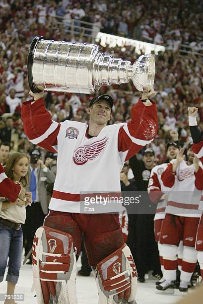 Goaltender Dominik Hasek of the Detroit Red Wings raises the Stanley Cup after eliminating the Carolina Hurricanes during game five of the NHL...