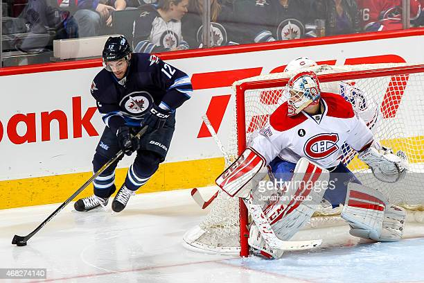 Goaltender Dustin Tokarski of the Montreal Canadiens guards the goal as he watches Drew Stafford of the Winnipeg Jets play the puck around the net...