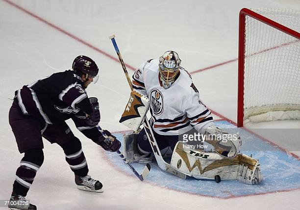 Goaltender Dwayne Roloson of the Edmonton Oilers makes a left leg pad save on a breakaway shot by Chris Kunitz of the Mighty Ducks of Anaheim in the...