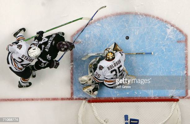Goaltender Dwayne Roloson of the Edmonton Oilers makes a save as Rob Niedermayer of the Mighty Ducks of Anaheim tries to play the rebound in the...
