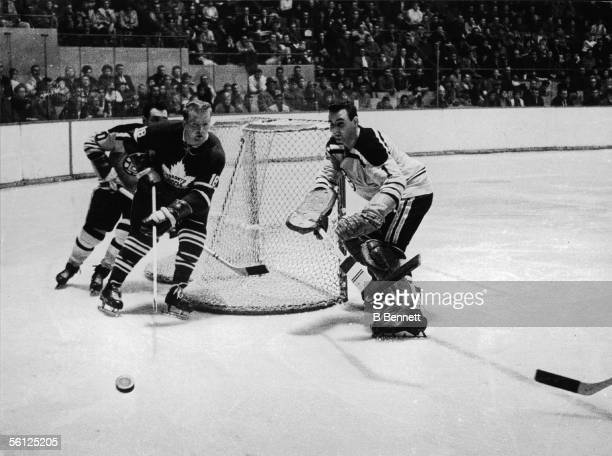 Goaltender Ed Johnston of the Boston Bruins skates around his net to confront Norm Armstrong of the Toronto Maple Leafs who is pursued by Leo Boivin...