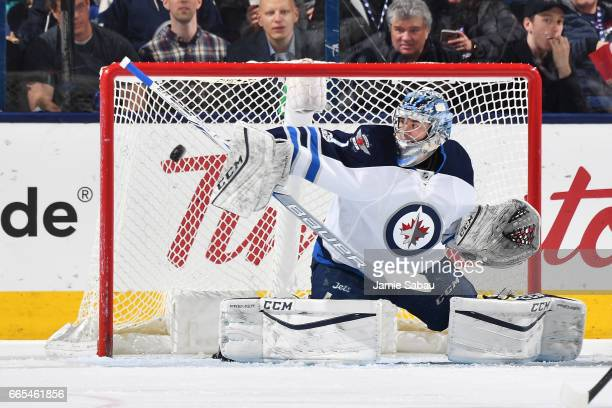 Goaltender Eric Comrie of the Winnipeg Jets blocks a shot during the first period of a game against the Columbus Blue Jackets on April 6 2017 at...