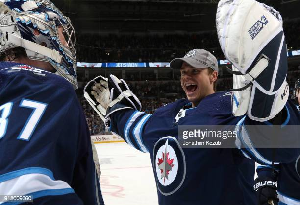 Goaltender Eric Comrie of the Winnipeg Jets congratulates teammate Connor Hellebuyck after backstopping the Jets to a 43 overtime victory over the...