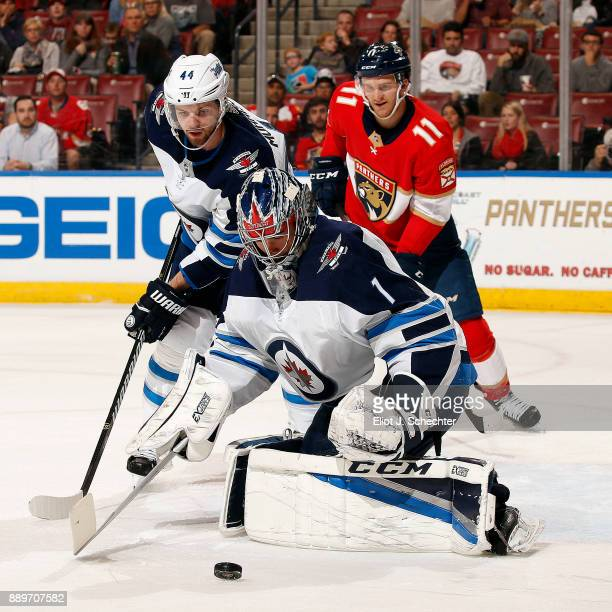 Goaltender Eric Comrie of the Winnipeg Jets defends the net with the help of teammate Josh Morrissey against Jonathan Huberdeau of the Florida...