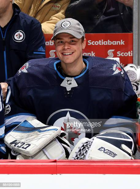 Goaltender Eric Comrie of the Winnipeg Jets is all smiles as he looks on from the bench prior to puck drop against the Ottawa Senators at the Bell...