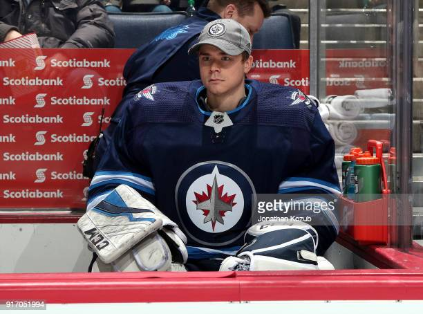 Goaltender Eric Comrie of the Winnipeg Jets looks on from the bench prior to puck drop against the New York Rangers at the Bell MTS Place on February...