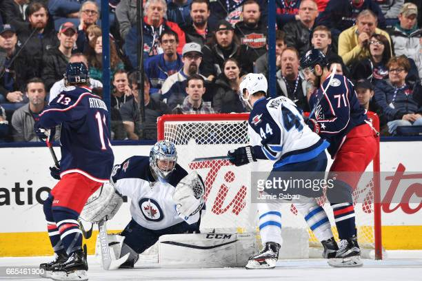Goaltender Eric Comrie of the Winnipeg Jets makes a glove save while players Josh Morrissey of the Winnipeg Jets and Nick Foligno of the Columbus...